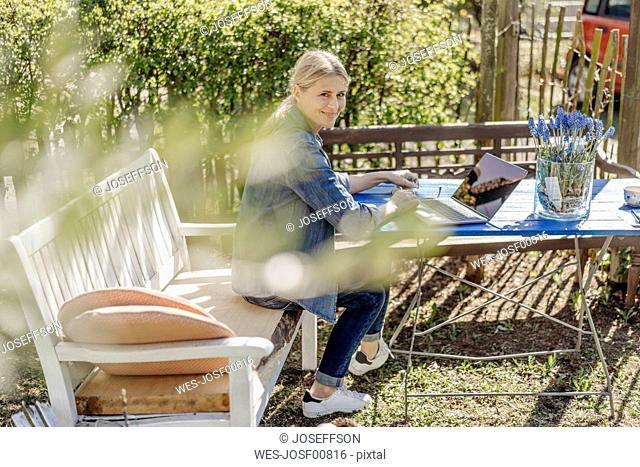 Smiling woman using laptop on garden bench