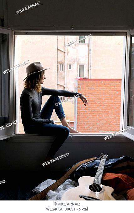 Young woman wearing a hat sitting in window frame