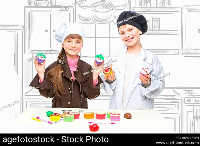 Beautiful boy and girl in chef clothes making christmas cupcakes. Children standing over kitchen drawing background