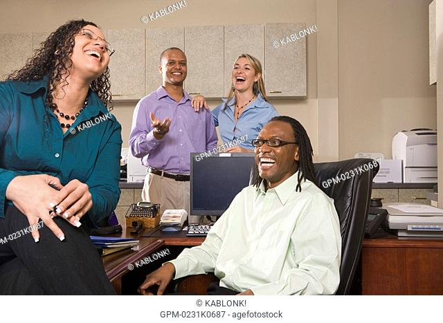 Four multi-ethnic businesspeople laughing in office around table