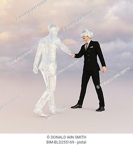 Businessman wearing virtual reality goggles shaking hands with transparent businessman