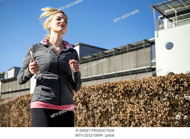 Woman in sportswear jogging and listening music on smart phone