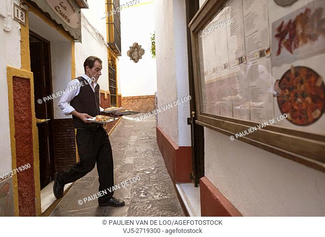 Sevilla, Spain, a waiter rushes from the kitchen to the other location to serve customers wih food