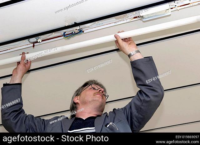 Elektriker repariert eine Deckenleuchte