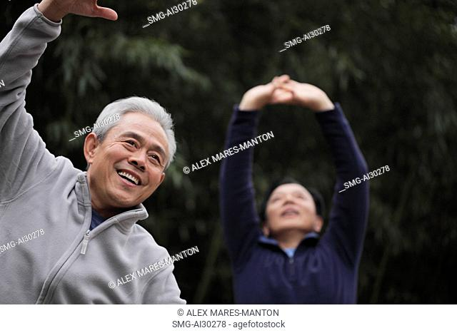 Two older men stretching outdoors