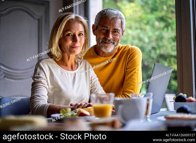 Portrait of smiling mature couple using laptop at home