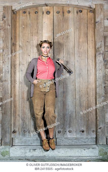 Young woman wearing traditional leather pants posing in front of a wooden door, dirndl look