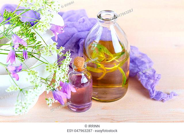 Mortar with fresh wild flowers and essential oil in glass bottles. Herbal medicine