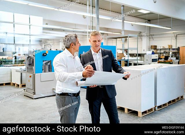 Two businessmen discussing a plan in a factory