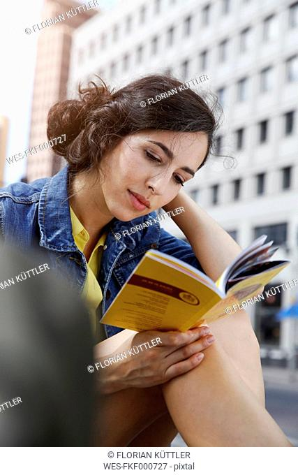 Germany, Berlin, portrait of young woman on city trip sitting at Potsdam Square reading guidebook