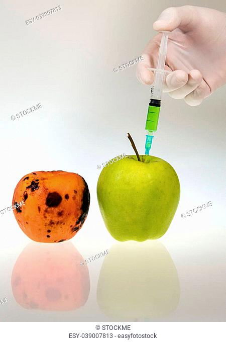Hand is injecting green chemicals into an apple. White and grey gradient background. High res photo taken with a full frame Nikon D610