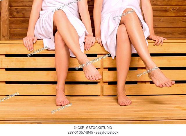 Girls in sauna. Cropped image of female legs in sauna