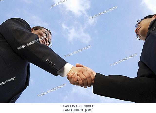 Two businessmen shaking hands, low angle view