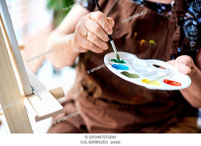 Woman holding palette with brush and paints