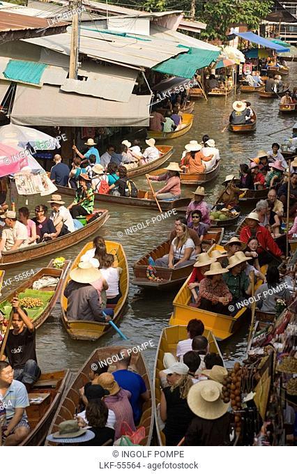 Tourists in a wooden boat visiting the Floating Market, Damnoen Saduak, near Bangkok, Ratchaburi, Thailand