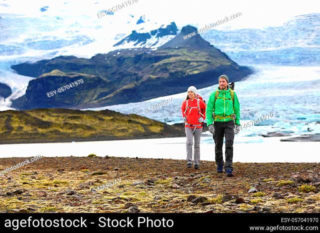 Adventure hiking travel couple trekking on Iceland. People by glacier and glacial lagoon / lake of Fjallsarlon, Vatna glacier, Vatnajokull National Park