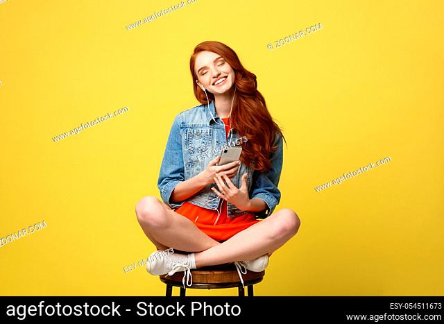 Lifestyle Concept: Pretty girl with long curly red hair enjoy listening to music on her phone and sitting on wooden chair on vivid yellow background in studio