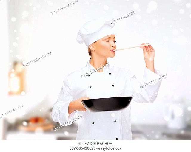 cooking, holidays, people and food concept - smiling female chef with pan and spoon tasting food over kitchen background