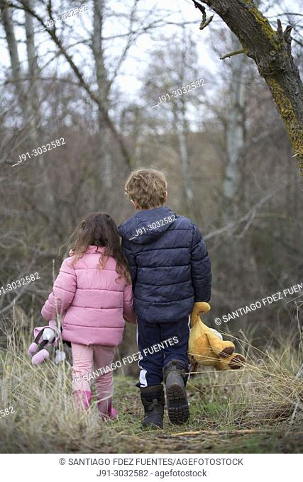 Two kids with their stuffed animals lost in forest