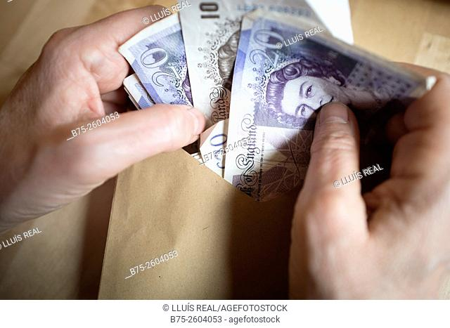 Woman hands counting banknotes pounds from an envelope