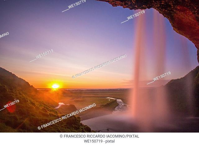 Iceland, Seljalandsfoss at sunset, waterfall and sunstar
