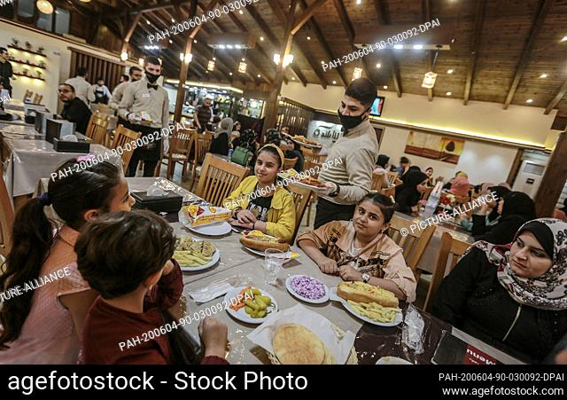 04 June 2020, Palestinian Territories, Gaza City: A waiter wearing a face mask serves people at a restaurant in Gaza City