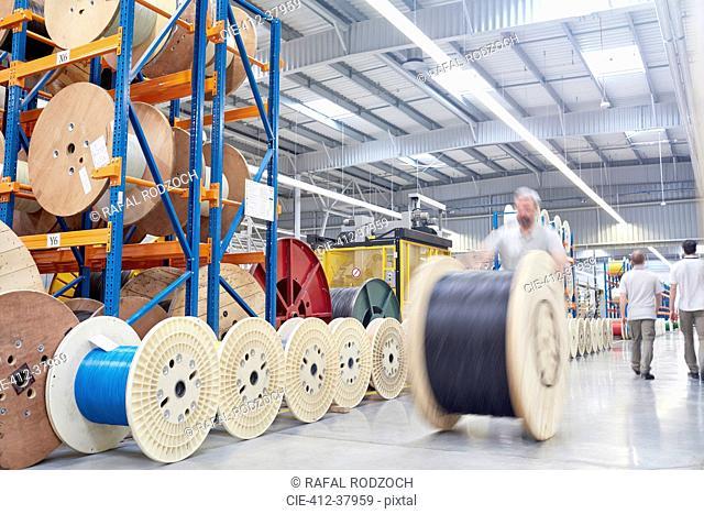 Male worker rolling large spool in fiber optics factory
