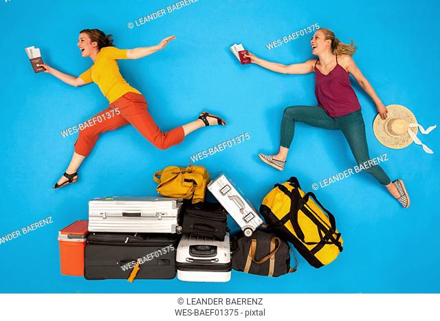Friends jumping over luggage , looking happy