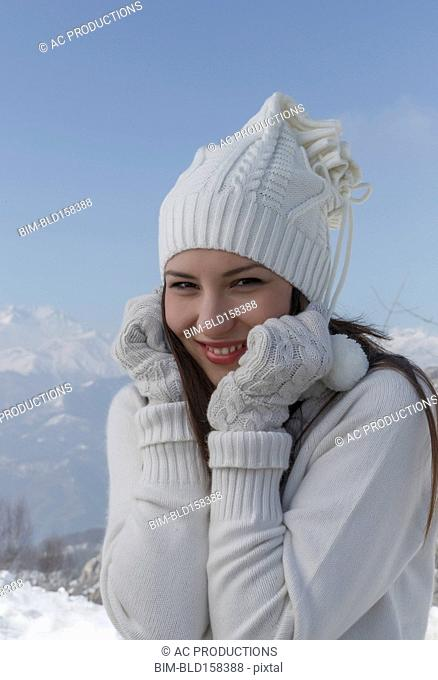 Caucasian woman wearing hat and gloves in snow