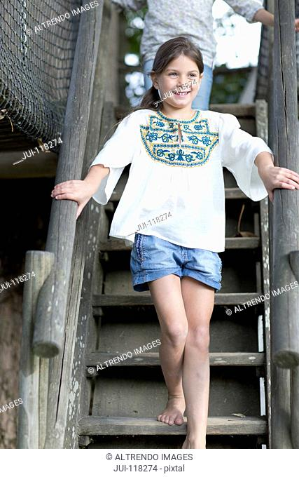 Young Girl Climbing Steps In Adventure Playground
