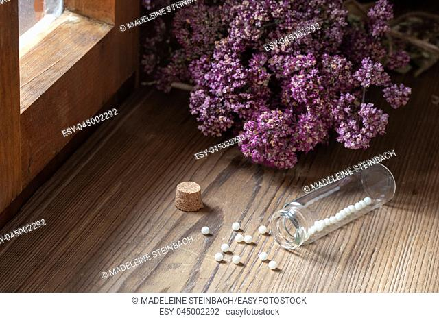 A bottle of homeopathic globules with dried herbs next to a window