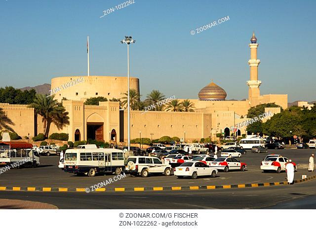 Taxis warten auf dem Platz vor der Festung und der Grossen Moschee, Nizwa, Sultanat Oman / Waiting taxis on the main square in front of the castle and the Grand...