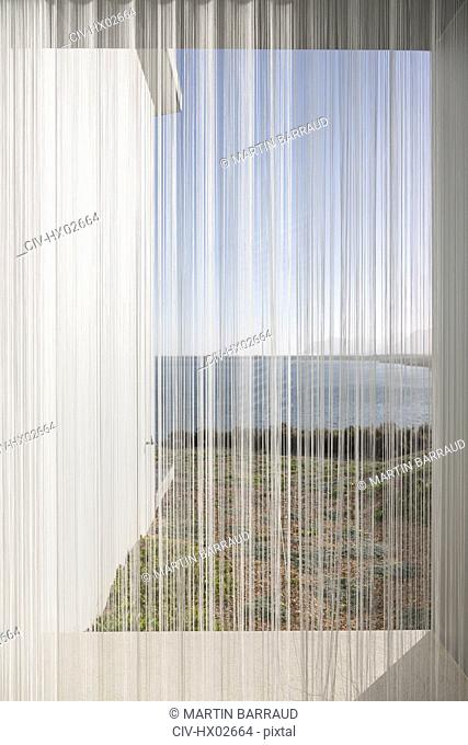 Gauze curtains in sunny, tranquil window with ocean view