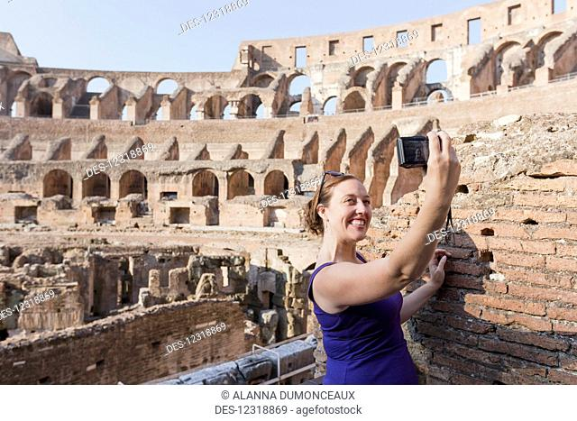 A young female tourist takes a selfie with her camera at the Roman Colosseum; Rome, Italy
