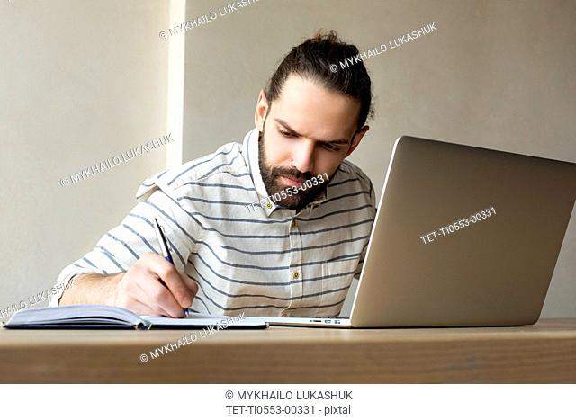 Young businessman with laptop writing in note pad