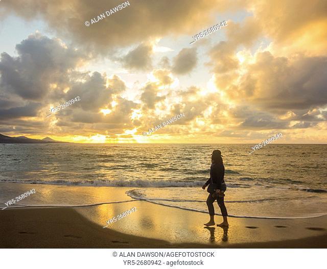 A woman walking along the city beach at sunset on Las Canteras beach in Las Palmas, Gran Canaria, Canary Islands, Spain