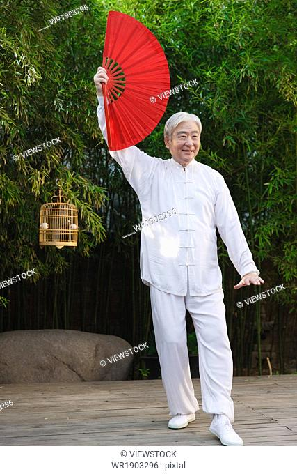 An old man holding a fan in the morning exercise