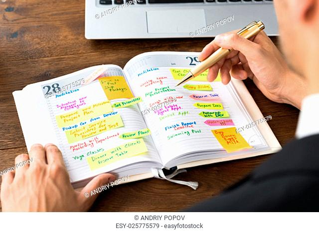 Close-up Of Businessperson Reading List Of Work In Diary
