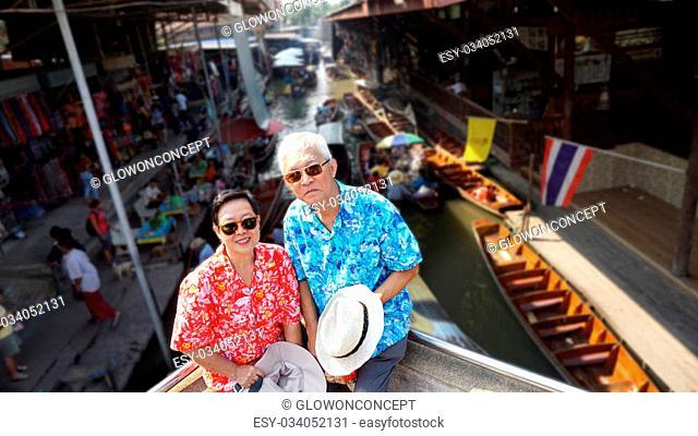Asian senior couple travel to thailand floating market exotic Landmark
