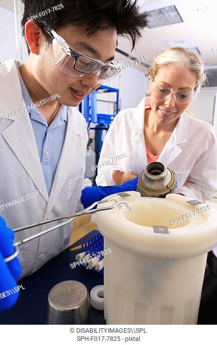 Engineering students using forceps while holding liquid nitrogen Dewar flask in water processing room in a laboratory