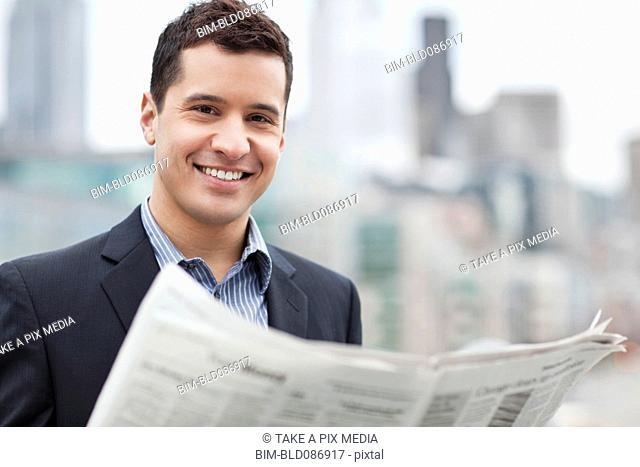 Mixed race businessman reading newspaper