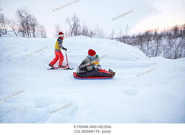 Mother and two sons on toboggan and snow scooter on snow covered hill, Hemavan,Sweden