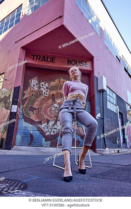 Australia, Adelaide, women's fashion blogger and actress Sarah Jeavons sitting on stool on street