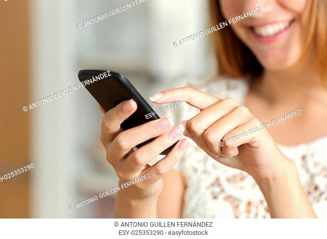 Close up of a woman hand texting on a smart phone at home with an unfocused background