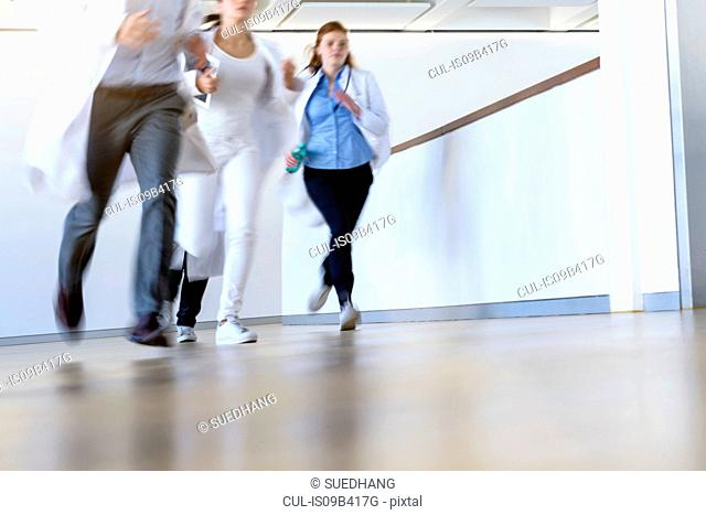Male and female doctors running along hospital corridor