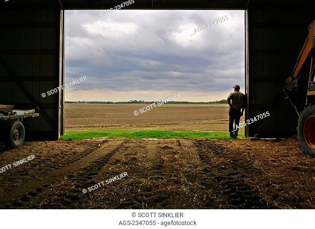Agriculture - A farmer standing at the entrance of his equipment barn looking out at approaching storm clouds and his prepared field prior to Spring planting /...
