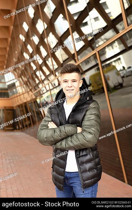Young crossed arms man standing against modern building
