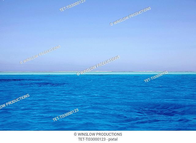 Clear sky above blue rippled sea