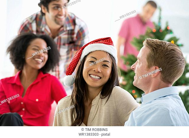 A woman wearing a red and white Father Christmas hat. At home. A decorated Christmas tree