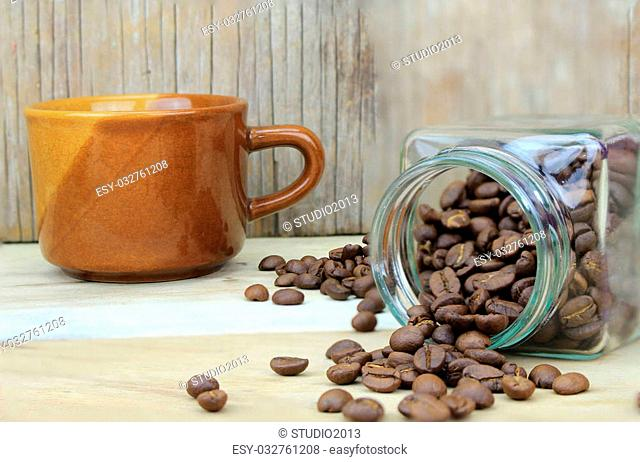 cup of coffee and coffee beans in glass bottle